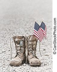 Alte Militärstiefel mit Hundemarken und zwei kleinen amerikanischen Flaggen