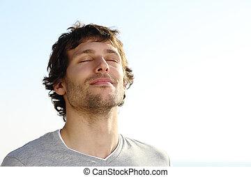 Attraktiver Mann atmet draußen.