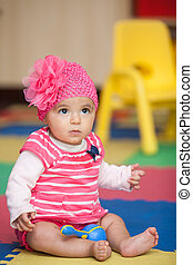 Baby-Mädchen in rosa mit einem Rumba-Shaker.