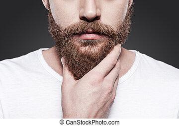 Berühren seinen perfekten Bart. Nahaufnahme des jungen, bärtigen Mannes, der seinen Bart berührt, während er vor grauem Hintergrund steht