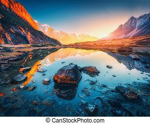 Berge mit beleuchteten Gipfeln, Steine im Bergsee bei Sonnenuntergang