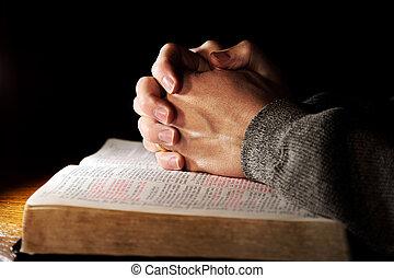 Beten Hände über eine heilige Bibel