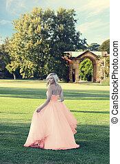 Blonde Frau in pfirsichfarbenem Tulpen-Ball-Kleid im formellen Garten.