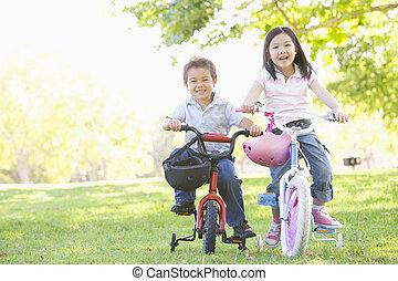 Bruder und Schwester lachen draußen auf Fahrrädern
