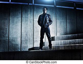 Cooler städtischer afroamerikanischer Mann auf distopischen Betonschritten