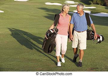 Das Senior-Paar läuft mit Taschen auf dem Golfplatz