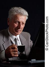 Den alten Mann in Anzug mit einer Tasse Kaffee