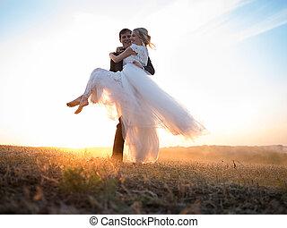 Der Ehemann trägt seine geliebte Frau in den Armen