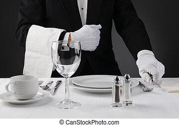 Der Kellner deckt den Tisch