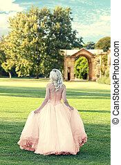 Der Rücken der Frau, die Abendkleider trägt, läuft im formellen Garten.