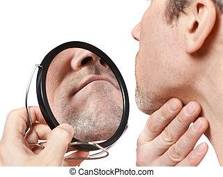 Der unrasierte Mann schaut in den Spiegel.