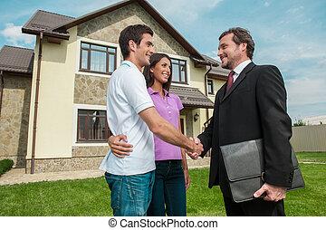 Der Verkäufer schüttet den Besitzern die Hand. Handshake kümmert sich draußen um junge Paare