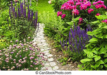 Der Weg in blühendem Garten.