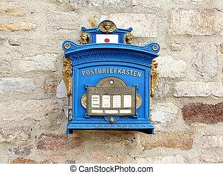 Deutscher blauer Briefkasten an der Mauer.