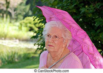 Die ältere Frau ruht sich im Garten aus