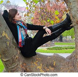 Die denkende Frau entspannt sich auf dem Baum und schaut lächelnd auf der Herbstfarbe