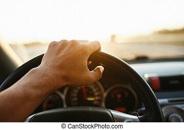 Die Hand des selektiven Fokus-Manns auf Lenkrad, Auto fahren bei Sonnenuntergang. Reisehintergrund