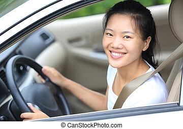 Die junge Asiatin fährt einen Wagen.