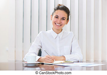 Die junge Frau in Weiß sitzt am Tisch.