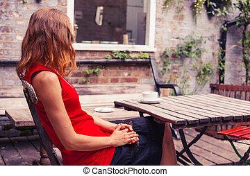 Die junge Frau sitzt am Tisch im Garten.
