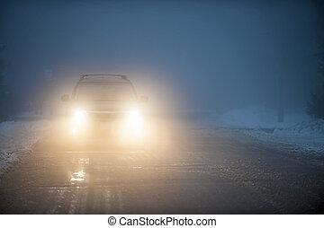 Die Scheinwerfer des Autos fahren im Nebel.