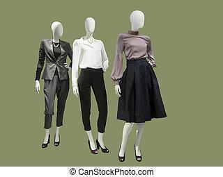 Drei weibliche Puppen mit modischen Kleidern.