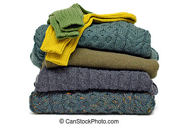 Ein Haufen dicker irischer Wolle, Kaschmir und Aran Winterspullover im Herbst und Winterfarben gegen Weiß