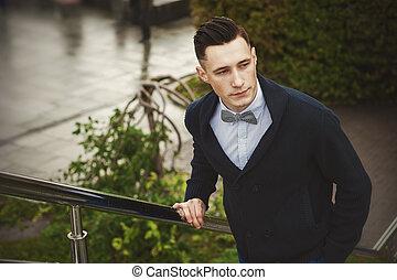 Ein junger, eleganter Mann draußen