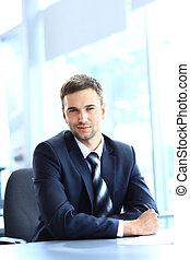 Ein junger Geschäftsmann, der im Büro arbeitet, sitzt am Schreibtisch.