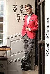 Ein junger, gutaussehender, stilvoller Mann, der sich in einem Haus aufhält.