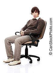 Ein junger Mann auf einem Stuhl