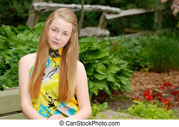 Ein junger Teenager sitzt im Garten