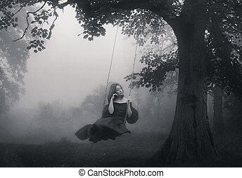 Ein junges Mädchen sitzt auf der Schaukel
