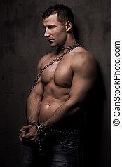 Ein junges männliches Model baut gut mit Ketten über seinem Körper