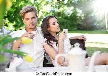 Ein junges Paar, das im Garten isst