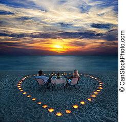 Ein junges Paar teilt ein romantisches Abendessen am Strand