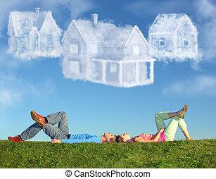 Ein lügendes Paar auf Gras und träumen drei Wolkenhäuser zusammen