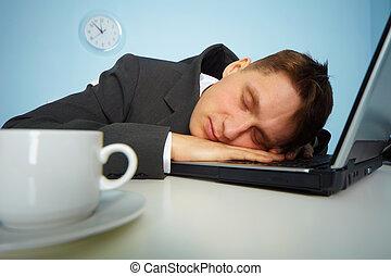 Ein müder Mann, der auf einem Notizbuch schläft