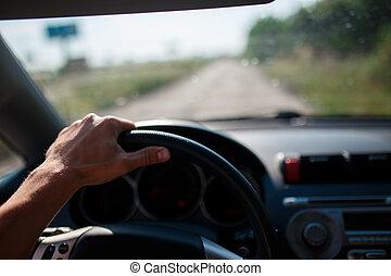 Ein Mann, der ein Auto fährt, konzentriert sich auf die linke Hand am Lenkrad.