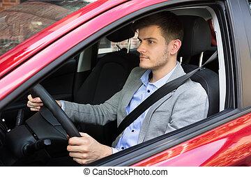Ein Mann, der rotes Auto fährt.