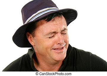 Ein Mann mit Hut weint