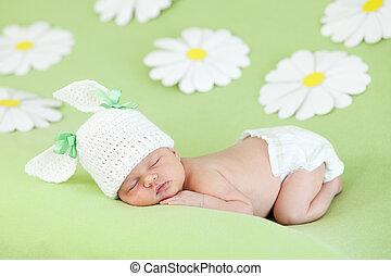 Ein Neugeborenes, das auf einer grünen Wiese zwischen Gänseblümchen schläft