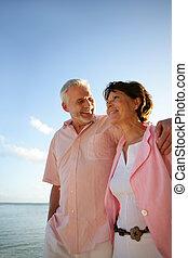 Ein Paar mittleren Alters, das einen Spaziergang am Strand macht