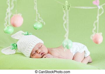 Ein reizendes Baby, gekleidet in Osterhasenmütze mit Eiern