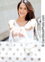 Eine fröhliche junge Frau, die einkauft