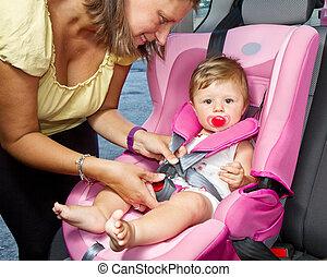 Eine Frau, die ihren Sohn auf einem Kindersitz in einem Auto festnimmt