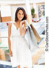 Eine Frau mit Einkaufstüten im Einkaufszentrum