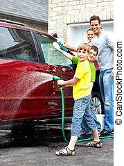 Eine glückliche Familie, die das Familienauto wäscht.