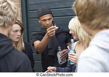 Eine Gruppe drohender Teenager, die draußen trinken