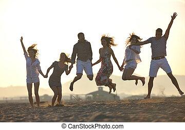 Eine Gruppe glücklicher junger Leute am Strand.